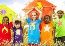 孩子不同的使用的风筝领域年轻人概念 免版税库存照片