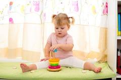 孩子与五颜六色的玩具的女孩戏剧在家 免版税库存照片