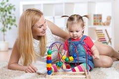 孩子与室内教育玩具的女孩戏剧 愉快 图库摄影