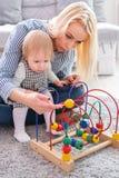 孩子与室内教育玩具的女孩戏剧 看她聪明的女儿的愉快的母亲 库存图片