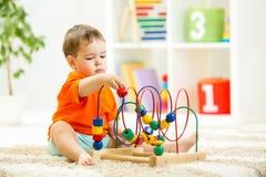 孩子与室内教育玩具的男孩戏剧 图库摄影
