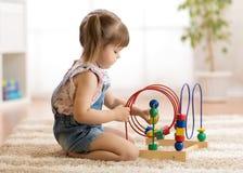 孩子与户内教育玩具的女孩戏剧 免版税库存照片