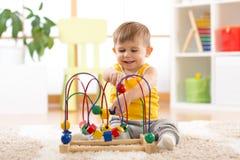 孩子与户内教育玩具的男孩戏剧 图库摄影