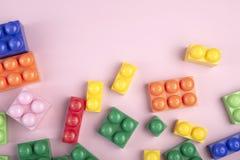 孩子与放置在桃红色桌的五颜六色的块的玩具背景 r 免版税库存图片