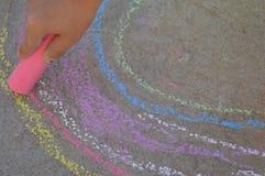 孩子与桃红色白垩的手图画在街道上 库存图片