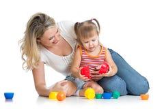 孩子与玩具一起的女孩和母亲作用 免版税图库摄影