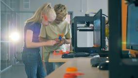 孩子与3D打印机一起使用 工作在一个科学实验室的男孩和女孩用印刷装置