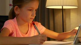 孩子为学习使用片剂,写家庭作业的女孩在夜互联网用法4K 影视素材