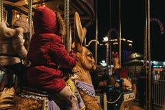 孩子乘坐旋转木马在冬天妙境圣诞节市场在伦敦,英国 免版税库存图片