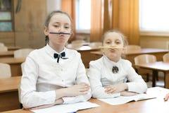 孩子于学校沉溺在教室做面孔模仿 免版税库存照片