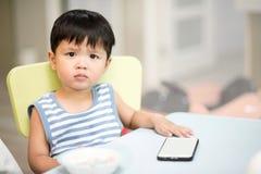 孩子亚洲与在桌上的一个手机 免版税库存图片