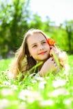 孩子享受春天晴天,当说谎在草甸时 季节性过敏概念 梦想的面孔的女孩拿着红色郁金香花 图库摄影