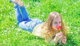 孩子享受郁金香芬芳,当说谎在草甸时 r 有说谎在grassplot,草的长发的女孩 免版税库存照片