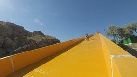 孩子从在水池的黄色水滑道滑了在室外水色公园 影视素材