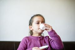 孩子从杯子喝着 图库摄影