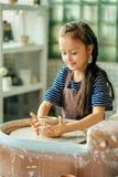 孩子从泥罐雕刻 塑造在横式转盘 库存图片