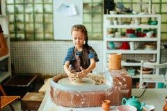 孩子从泥罐雕刻 塑造在横式转盘 库存照片