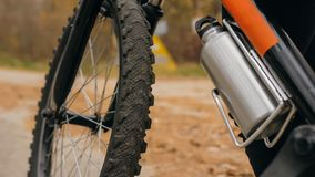 孩子从铝烧瓶的饮料水 一白种人儿童乘驾在秋天公园骑自行车路 女孩骑马黑色 库存图片
