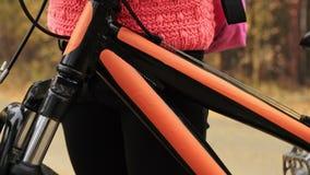 孩子从铝烧瓶的饮料水 一白种人儿童乘驾在秋天公园骑自行车路 女孩骑马黑色 股票视频