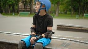 孩子体育爱好路辗男孩坐的等待的冰鞋 股票视频