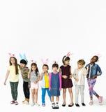 孩子佩带复活节幸福的兔宝宝耳朵微笑在白色背景的小组 库存照片