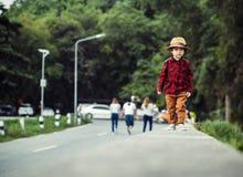孩子佩带帽子和走在路 免版税库存图片