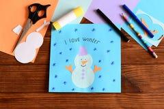 孩子使一个滑稽的纸雪人补花,画了雪花并且写了I爱冬天 文具,色纸在桌上覆盖 免版税库存图片