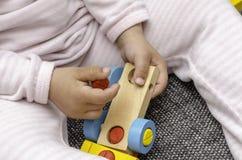 孩子使用与一辆五颜六色的木汽车 免版税库存照片