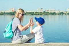 孩子使用与他的母亲 走沿堤防 库存图片