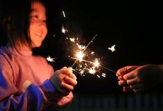 孩子使用与在节日的火闪烁发光物 免版税图库摄影