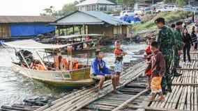 孩子使用与战士在劈裂的码头的一条小船附近 库存图片