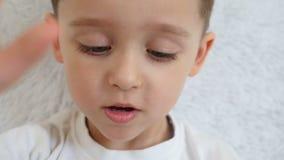 孩子使用与智能手机 移动照相机向您的孩子的脚、电话和面孔,特写镜头 股票录像