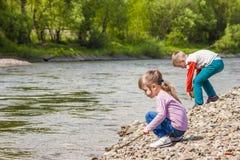 孩子使用在河附近的男孩和女孩 免版税库存照片