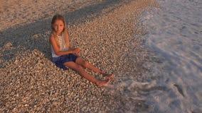 孩子使用在海滩的,在日落的孩子,在海水的女孩投掷的小卵石 免版税图库摄影