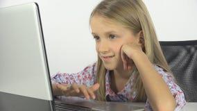 孩子使用在膝上型计算机的,学习个人计算机,女孩画象的孩子学会在学校课程 库存图片
