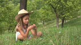 孩子使用在草的,孩子放松在果树园的室外,女孩本质上,夏天