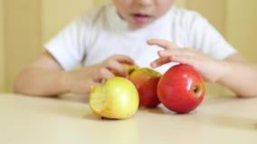 孩子使用用在桌上的苹果 特写镜头 照相机的焦点是瞄准的苹果 股票录像