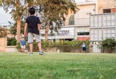 孩子使用footbal在绿草,在家庭菜园 免版税库存图片