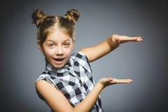 孩子保留某事在手之间 特写镜头画象英俊女孩微笑 免版税库存照片