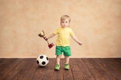 孩子假装是足球运动员 免版税库存图片