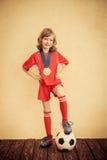 孩子假装是足球运动员 免版税库存照片