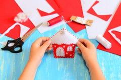 孩子做了一件毛毡圣诞树房子装饰品 孩子在他的手上拿着圣诞节房子装饰品 工具和材料缝合的 免版税库存照片
