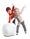 孩子做在冬时的一个雪人,被隔绝 库存照片