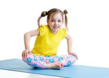 孩子做坐在蝴蝶姿势的体操 免版税库存图片