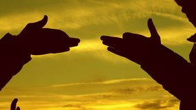 孩子做形状狗形状用手在日落 女孩举行一个狗标志的姿态与他们的手指的反对 股票视频