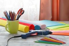 孩子做装饰纸 胶浆,剪刀,色纸 免版税库存图片
