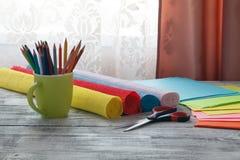 孩子做装饰纸 胶浆,剪刀,色纸 图库摄影