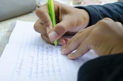 孩子做他的家庭作业 数学的笔记本 手举行笔 B 免版税库存照片