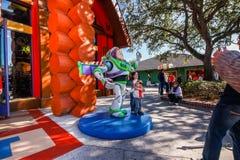 孩子停留在宇航员雕塑靠近玩具商店 免版税库存图片