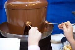 孩子儿童` s生日聚会,戏耍和果子的巧克力喷泉能浸洗 免版税图库摄影
